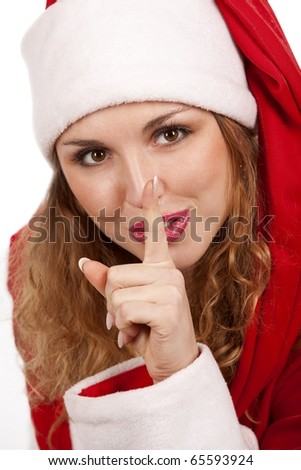 Santa girl  is putting her finger on lips and looking with a smile. Isolated on white. - stock photo
