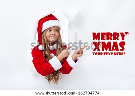 Santa girl pointing to copy space - leaning through hole in paper