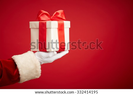 Santa hand holding giftbox with surprise - stock photo