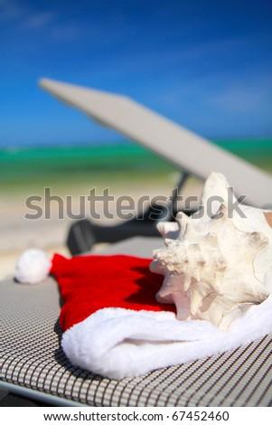 Santa Hat and seashell on chaise longue on caribbean sea - stock photo