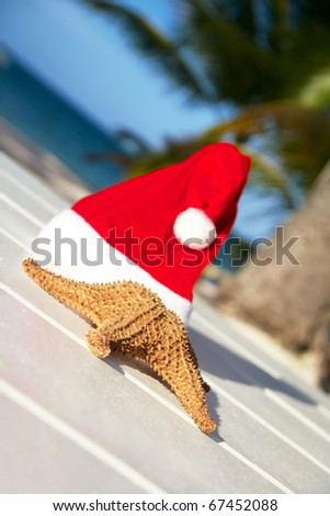 Santa hat and starfish on wooden table , caribbean beach - stock photo