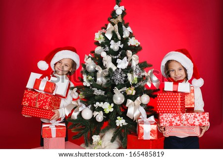 Santa hat Christmas girls holding christmas gifts smiling happy and excited. Cute beautiful santa children on red background.