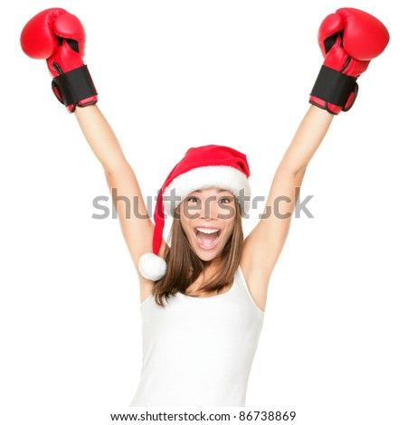 Santa hat christmas woman celebrating wearing boxing gloves. Fitness or boxing shopping day concept. Winner energy from asian caucasian female model isolated on white background. - stock photo