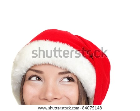 Santa hat christmas woman looking up - closeup of beautiful christmas girl with smiling eyes looking at copy space isolated on white background.