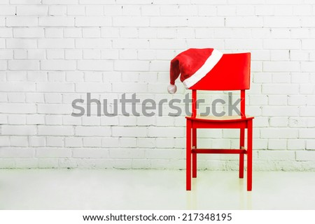 Santa hat hanging on a chair against brick wall. Christmas concept - stock photo