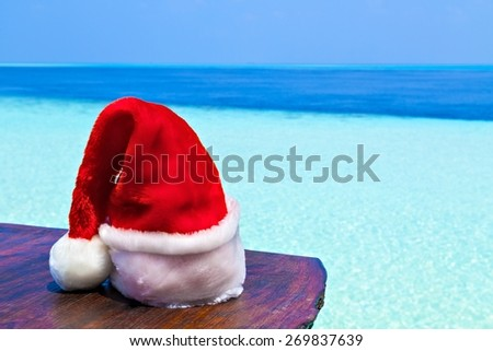 Santa hat is on a beach table, Maldives, The Indian Ocean - stock photo
