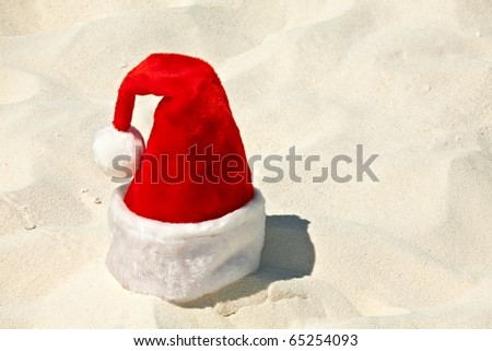 Santa hat is on a coral sandy beach - stock photo