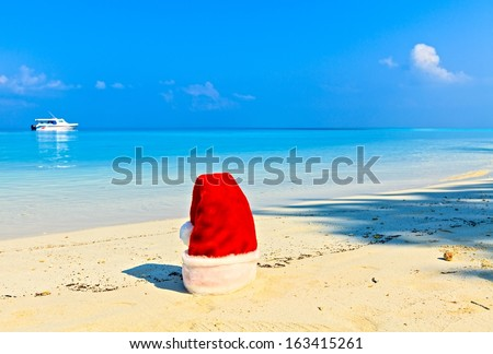 Santa hat is on coral sandy beach - stock photo