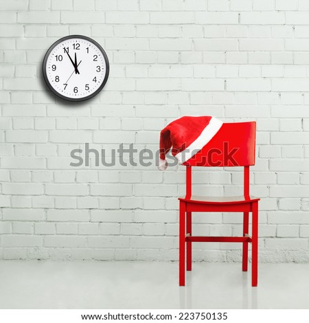 Santa hat on a chair against brick wall with clock. Christmas concept - stock photo