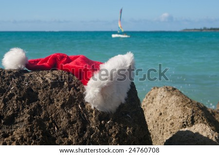 Santa hat on a rock with a holiday sea in the background. There is a small boat sailing in the distance - stock photo