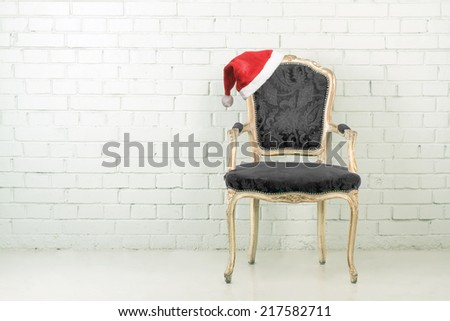 Santa hat on a vintage armchair. Brick wall with copy space - stock photo