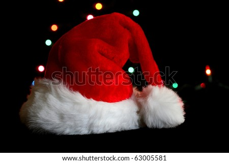 Santa hat on black background with holiday lights