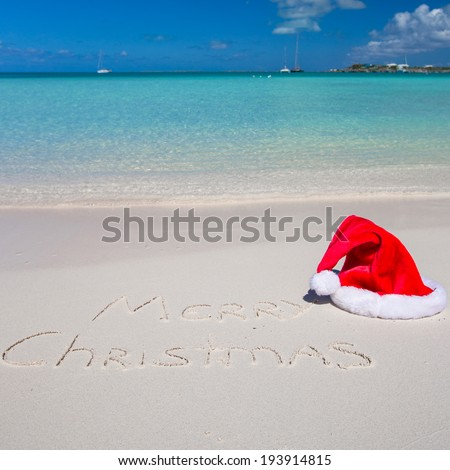 Santa Hat on white sandy beach and Merry Christmas written in the sand - stock photo