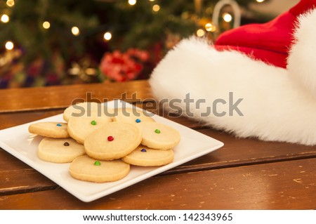Santa hat with a plate of shortbread cookies - stock photo