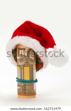 Santa hat with fifty euro banknote on bright background - stock photo