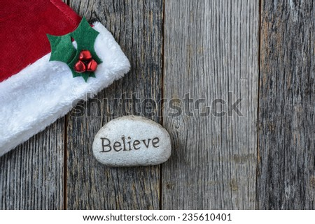 Santa Hat with the text Believe on a Stone Rock on Wood Background - stock photo