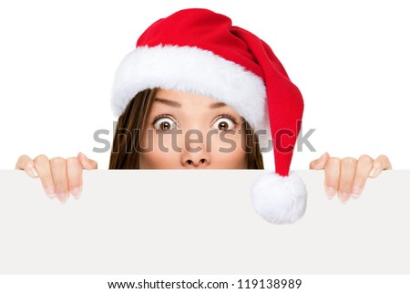 Santa hat woman showing christmas sign peeking over edge wearing red santa hat with funny expression. Mixed race asian chinese / caucasian woman portrait isolated on white background. - stock photo