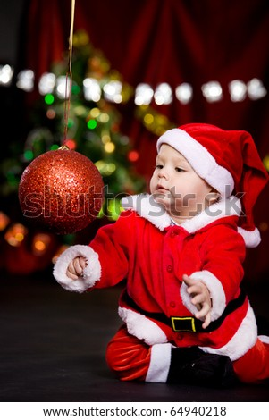 Santa helper playing with large Christmas ball - stock photo