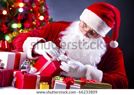 Santa holding a gift box while wrapping it up - stock photo