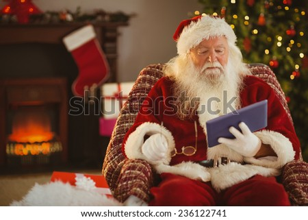 Santa holding his glasses and using tablet at home in the living room - stock photo