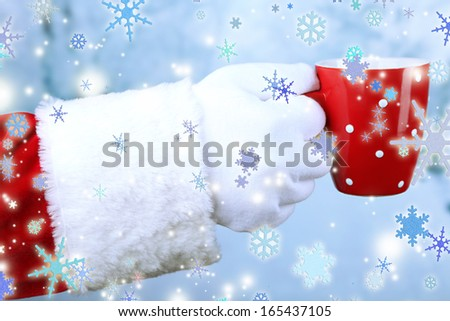 Santa holding mug in his hand, on light background