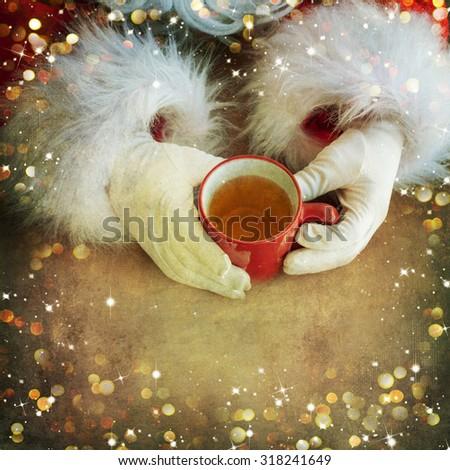 Santa holding mug of tea - stock photo