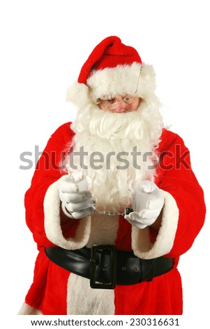 Santa in Hand Cuffs. Santa Claus has been a Bad Bad Boy this year. Perhaps he had one to many Brandy Alexander's or Too Many Cookies or went down the chimney of an Unbeliever and they called the cops. - stock photo