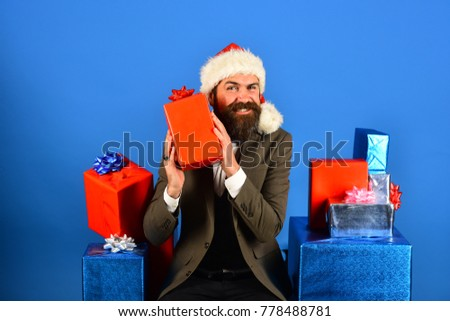 Santa in retro suit presents blue and red gifts on blue background. Businessman with curious smile and stack of boxes. New year eve concept. Man with beard holds presents.