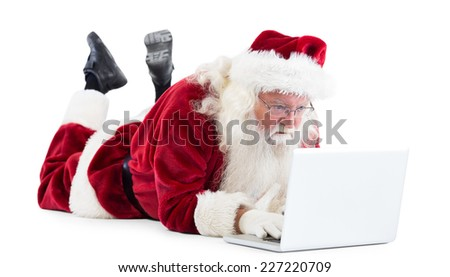 Santa lies in front of his laptop on white background - stock photo