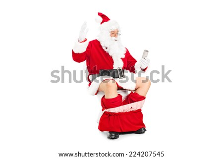 Santa looking at an empty toilet paper roll seated on a toilet isolated on white background - stock photo