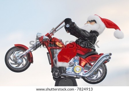 Santa looking cool with a bit of an attitude on his shiny new red and chrome chopper. - stock photo