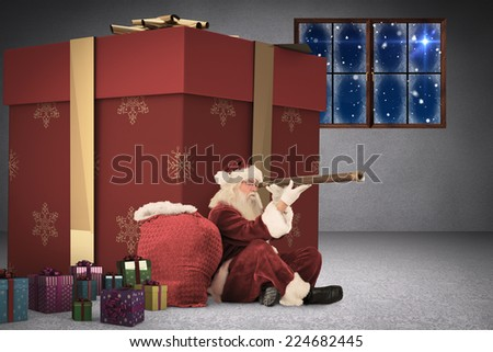 Santa looking through a telescope against grey room - stock photo