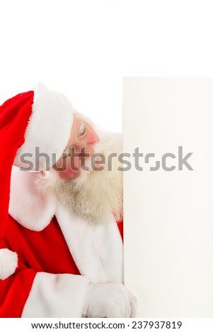Santa looks around the side at the blank white sign he is holding.  Room for your Copy that Santa is looking at. - stock photo