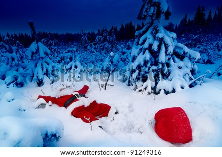 Santa lying in the snow with his presents sack near him - stock photo