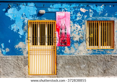 SANTA MARIA, CAPE VERDE - DECEMBER 16, 2015: Coca cola red weathered sign on a blue flaking paint wall. Yellow grilled window and door