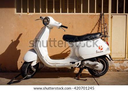 SANTA MARIA, CAPE VERDE - DECEMBER 16, 2015: Old white Vespa Scooter, secured by the wall - stock photo
