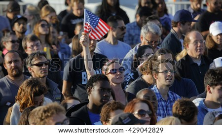 SANTA MONICA, CA - MAY 23, 2016: Female with US Flag is supporter of Bernie Sanders (D - VT) at a Presidential rally at Santa Monica High School Football Field in Santa Monica, California.