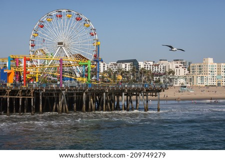 Santa Monica, California, USA - April 18, 2014: Tourists ride the roller coaster at Pacific Park amusement grounds on Santa Monica Pier