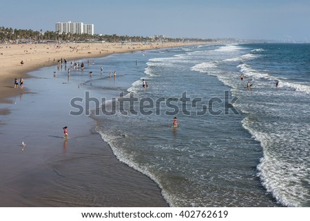 Santa Monica, California, USA - March 18, 2014: Tourists, local residents and families gather in the sunshine on Santa Monica Beach - stock photo