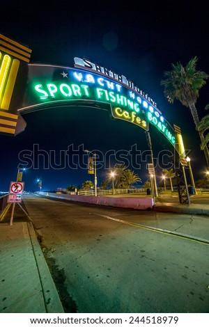 SANTA MONICA - JAN 14, 2015: Famous Santa Monica Yacht Harbor Sign - Entrance to Santa Monica Pier on Ocean Avenue in LA at Night. Santa Monica is a beachfront city in Los Angeles California. - stock photo