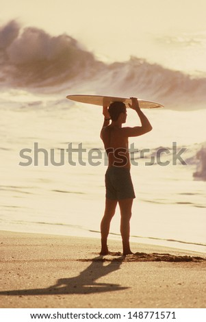 SANTA MONICA, LOS ANGELES, CA  - CIRCA 1980's: Young surfer carrying surfboard on his head in Santa Monica, CA - stock photo