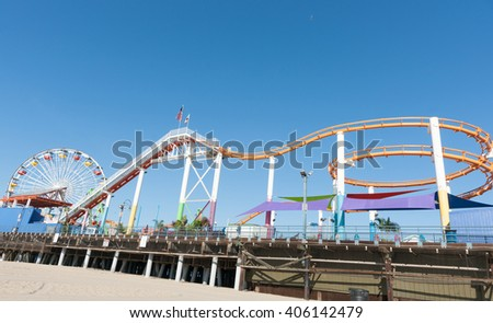 Santa Monica Pier rides and attractions colorful roller coaster structure snaking along pier under blue sky - stock photo