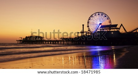 Santa Monica Pier silhouetted against a sunset and reflected in the wet sand of the beach - stock photo