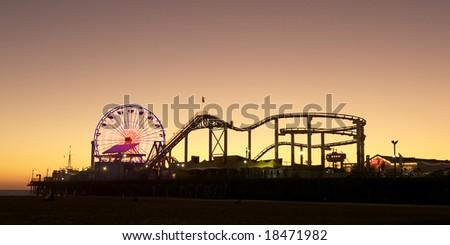 Santa Monica Pier silhouetted against the setting Californian sun - stock photo