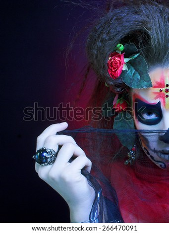 Santa Muerte. Young woman with creative visage and with roses in her hair. - stock photo