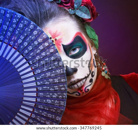 Santa Muerte. Young woman with creative visage and with roses in her hair and with blue fan. - stock photo