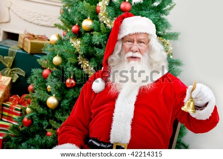 Santa next to a Christmas tree holding a bell - stock photo