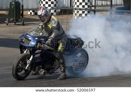 SANTA POD, UK - APRIL 23: Alternative energy racing at Santa Pod Raceway. A burnout by Andy Gilbert on his 150mph biofuel powered Suzuki motorcycle. April 23, 2010, Santa Pod, UK.