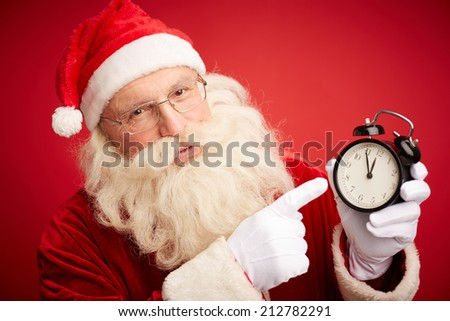 Santa pointing at clock showing five minutes to midnight - stock photo