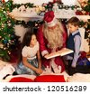 Santa reading Christmas book to kids sitting by decorated tree with boy and girl - stock photo